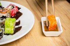 Il rotolo di sushi ha fatto il assorti del piatto Bastoncini con rotolo, souce del dado Immagini Stock