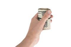 Il rotolo torto dei dollari ha stretto l'elastico nella mano Fotografia Stock Libera da Diritti