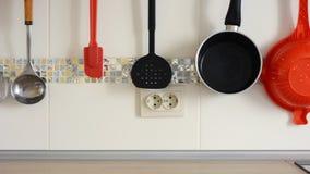 Il rubinetto sta versando l'acqua e gli utensili della cucina appendono sui precedenti delle piastrelle di ceramica bianche archivi video