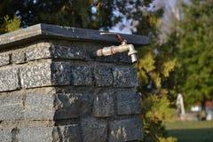 Il rubinetto sul pozzo della pietra Fotografia Stock Libera da Diritti