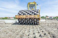 Il rullo compressore enorme con le punte sta comprimendo il suolo a costruzione fotografia stock