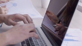 Il ` s degli uomini passa il tipo testo sul computer portatile accanto alla donna che scrive la penna su carta video d archivio