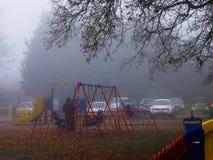 Il ` s dei bambini oscilla la mattina nebbiosa nel parco dell'erpice Fotografie Stock