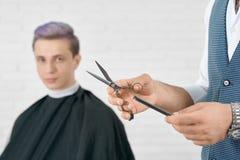 Il ` s del barbiere passa la tenuta le forbici metalliche e del pettine di plastica nero immagini stock libere da diritti