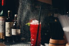 Il ` s del barista passa la spruzzatura del succo nel vetro di cocktail riempito di bevanda alcolica sui precedenti scuri Immagine Stock Libera da Diritti