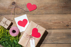 Il ` s del biglietto di S. Valentino ha decorato il contenitore di regalo sopra fondo di legno Vista da Immagini Stock