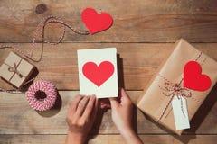 Il ` s del biglietto di S. Valentino ha decorato il contenitore di regalo sopra fondo di legno Vista da Immagine Stock Libera da Diritti