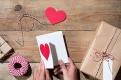 Il ` s del biglietto di S. Valentino ha decorato il contenitore di regalo sopra fondo di legno Vista da Fotografia Stock