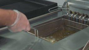 Il ` s del cuoco unico passa il versamento della patata ad una friggitrice per la cottura delle patate fritte archivi video