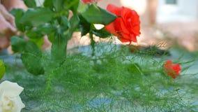 Il ` s del fiorista della donna passa la fabbricazione del mazzo con le rose sulla tavola per il negozio di fiore archivi video
