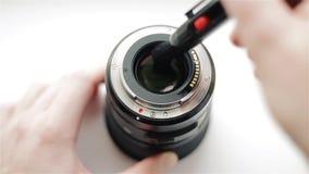 Il ` s del fotografo passa pulito il lato posteriore della lente moderna da polvere con una matita professionale a cura per video d archivio
