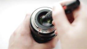 Il ` s del fotografo passa pulito il lato posteriore della lente moderna dalla sporcizia e delle impronte digitali con una matita stock footage