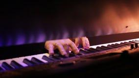 Il ` s del giocatore di piano passa il gioco della musica al concerto di notte con le luci impressionanti stock footage