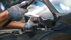 Il ` s del meccanico passa alla riparazione l'automobile con un martello archivi video