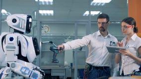Il ` s del robot del controllo della donna e dell'uomo funziona video d archivio
