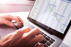 Il ` s dell'uomo d'affari passa lavorare al diagramma di Gantt sul computer portatile immagine stock