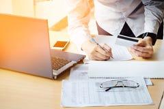 Il ` s dell'uomo di affari passa la tenuta del documento di pagamento di scrittura della carta di credito immagini stock