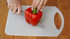 Il ` s della donna passa affettare il peperone su un tagliere di legno archivi video