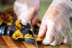 Il ` s della donna passa affettare le prugne su un bordo di legno Fotografia Stock Libera da Diritti