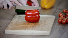 Il ` s della donna passa affettare il peperone dolce rosso dolce su un tagliere di legno stock footage