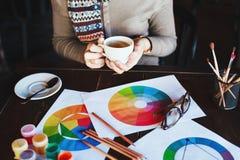 Il ` s della donna passa il tè, le pitture, le spazzole ed i disegni della tenuta sulla tavola Immagine Stock Libera da Diritti