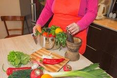 Il ` s della donna passa la cottura del pasto sano nella cucina, dietro gli ortaggi freschi Fotografie Stock Libere da Diritti