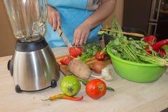 Il ` s della donna passa la cottura del pasto sano nella cucina, dietro gli ortaggi freschi Immagine potata delle verdure di tagl Fotografia Stock