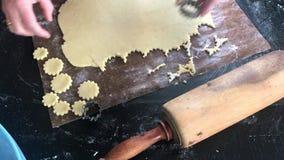 Il ` s della donna passa la fabbricazione intorno ai biscotti a forma di di natale archivi video