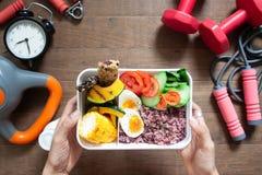 Il ` s della donna passa la scatola di pranzo della tenuta con la bacca del riso, gli uova sode, interruttore fotografia stock