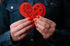 Il ` s della donna passa la tenuta del cuore rosso dolce Fine in su immagine stock