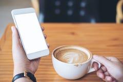Il ` s della donna passa la tenuta del telefono cellulare bianco con lo schermo in bianco e la tazza di caffè macchiato di latte  immagine stock