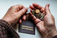 Il ` s della donna passa la tenuta delle monete russe sopra il certificato di pensione immagini stock libere da diritti