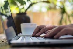 Il ` s della donna passa il lavoro e la battitura a macchina sulla tastiera del computer portatile sulla tavola di legno con il f Fotografia Stock Libera da Diritti
