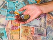 Il ` s della donna passa le monete della tenuta oltre 10, 20, 50, 100, 200, 500 e 2000 rupie indiane fotografie stock libere da diritti