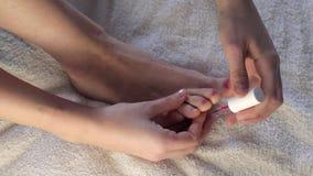 Il ` s della donna passa le unghie del piede della pittura Ragazza che dipinge i suoi chiodi sulla lacca di rosa del piede stock footage