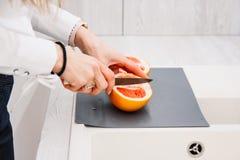 Il ` s della donna passa il taglio del pompelmo fresco sulla cucina Ragazza che taglia arancia con il coltello Concetto sano di s immagini stock libere da diritti