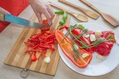 Il ` s della donna passa a taglio il peperone dolce, dietro gli ortaggi freschi Fotografie Stock