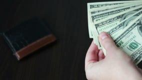 Il ` s delle donne passa la tenuta del fan di cento banconote in dollari e conteggi stock footage