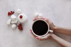 Il ` s delle donne passa la tenuta della tazza di caffè su un fondo bianco Immagini Stock