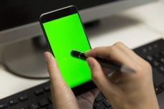 Il ` s delle donne passa lo schermo del telefono di tocchi con la penna per lo schermo attivabile al tatto mob fotografia stock libera da diritti