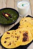 Il saag punjabi del pasto-Sarso (verdi) è servito con il pane piano indiano del mais (makka) Immagine Stock