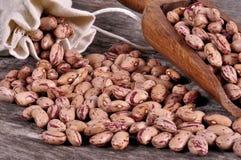 Il sacco dei fagioli della miscela rovescia i fagioli con i fagioli sulla tavola di legno Fotografia Stock