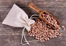 Il sacco dei fagioli della miscela rovescia i fagioli con i fagioli sulla tavola di legno Immagine Stock Libera da Diritti
