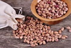 Il sacco dei fagioli della miscela rovescia i fagioli con i fagioli sulla tavola di legno Immagine Stock