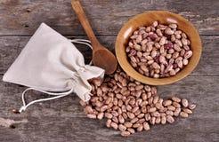Il sacco dei fagioli della miscela rovescia i fagioli con i fagioli sulla tavola di legno Fotografie Stock Libere da Diritti