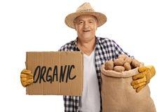 Il sacco ed il cartone anziani della tela da imballaggio della tenuta dell'agricoltore firmano Fotografia Stock