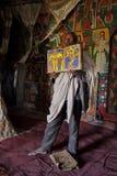 Il sacerdote apre una bibbia illustrata dentro una chiesa in Etiopia Immagini Stock