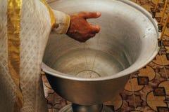 Il sacerdote benedice l'incrocio cadendolo nella fonte con acqua, il battesimo, la chiesa, il simbolo Chiesa ortodossa Il tradit immagine stock libera da diritti