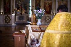 il sacerdote che sta con il suo di nuovo all'altare nella chiesa ortodossa del tempio Fotografia Stock