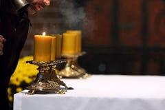 Il sacerdote mette fuori le candele sull'altare dopo Massachussets nella c Fotografie Stock Libere da Diritti